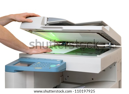 Hands putting a sheet of paper into a copying device, isolated on white - stock photo