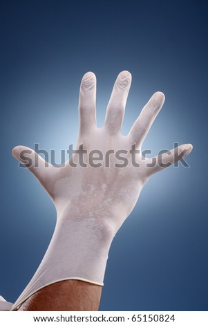 Hands putting on surgical gloves over a creative blue background. - stock photo