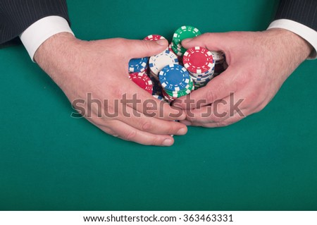 hands rakes the pile of poker chips - stock photo