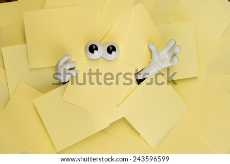Hands reach out and eyes peer out from under several bright yellow sticky notes. - stock photo