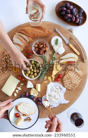 Hands reaching for food on a well spread cheese platter, party snack appetiser with wine - stock photo