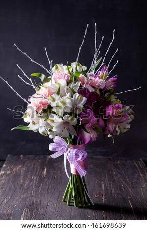Hands receiving a pastel bouquet from pink and purple gilly flowers