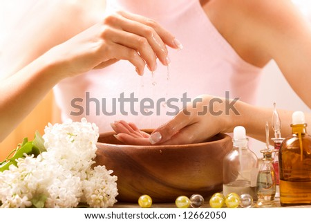 Hands relaxing in bowl of water with rose petals. French manicure. - stock photo