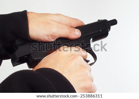 Hands reload semi-automatic handgun on a white background - stock photo