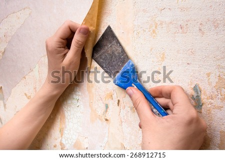 Hands removing wallpaper from wall with spatula - stock photo