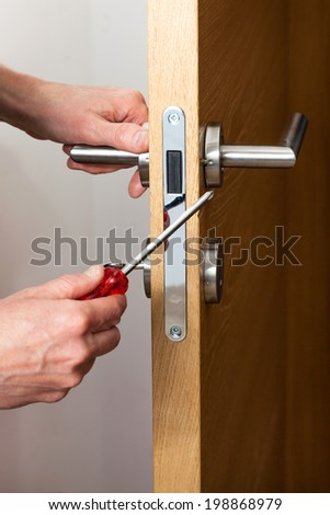 Hands repairing a door lock with a screwdriver - stock photo
