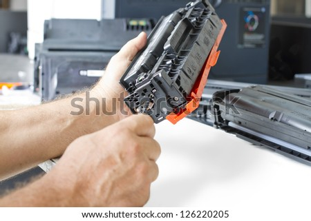 hands repairing laser toner cartridge - stock photo