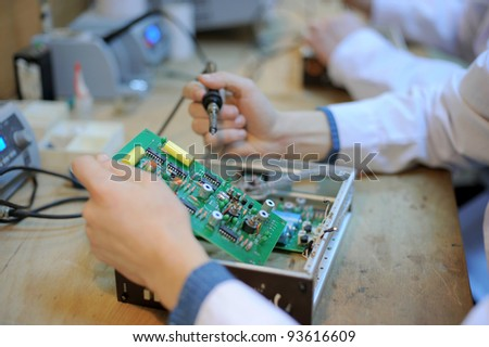 Hands repairing of microcircute with solderer - stock photo