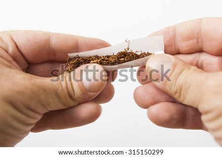 Hands rolling a cigarette with rolling tobacco on white background - stock photo