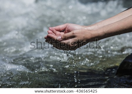 Hands sachibalaya clean water from the mountain stream bubbling