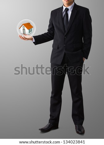 hands saving small home in glass ball - stock photo
