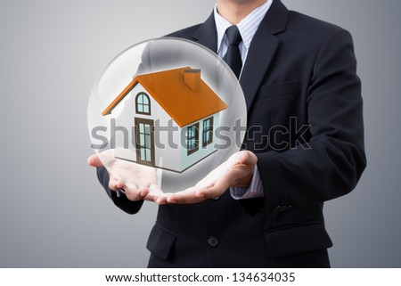 hands saving small house in crystal ball - stock photo
