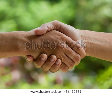 hands shake over nature background - stock photo