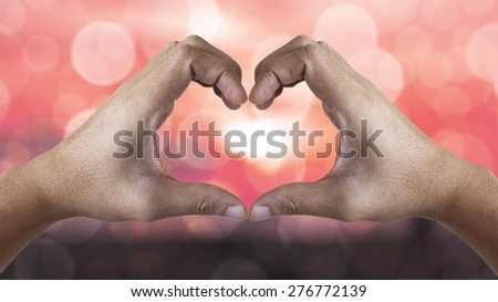 Hands shaping a heart symbol on Bokeh blurry background - stock photo