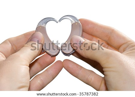 Hands showing a heart shape from digital hearing aids. Isolated on white. - stock photo