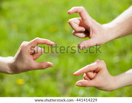 Hands showing different sizes - from small to big, natural green  background - stock photo
