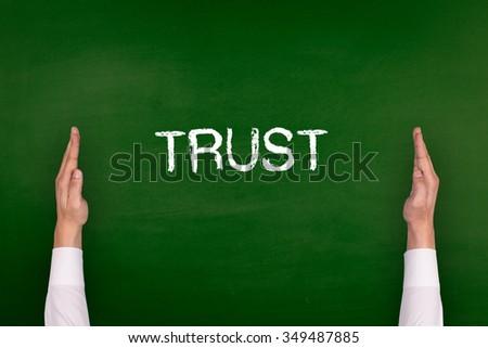 Hands Showing TRUST on Blackboard - stock photo