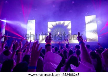 Hands silhouette on a concert in the center  - DJ visible on the stage. Pink rays laser show. - stock photo