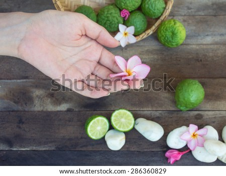 Hands spa with Kaffir Lime and flowers on wooden background - stock photo