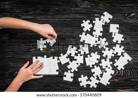 hands starting to collect puzzle pieces - stock photo