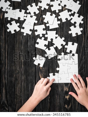 hands starting to collect puzzle pieces on dark wooden table - stock photo