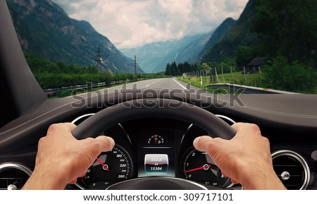 Hands steering wheel. Highway car driving. - stock photo