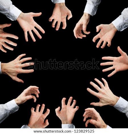 Hands stretching to something isolated on black background - stock photo