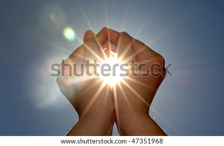 Hands surrounding the sun - stock photo