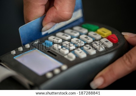 Hands swiping magnetic card on pos terminal - stock photo
