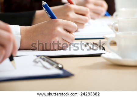Hands taking notes. - stock photo