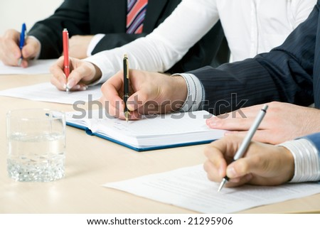 Hands taking notes, focus is on the pen - stock photo