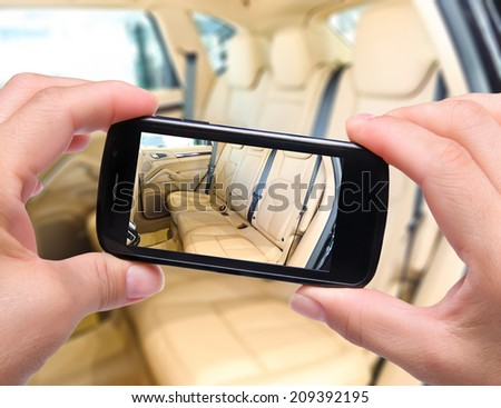 Hands taking photo  car interior with smartphone - stock photo