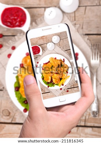 Hands taking photo chicken wings with smartphone - stock photo