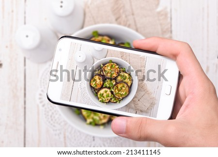 Hands taking photo fried eggplant  with smartphone - stock photo