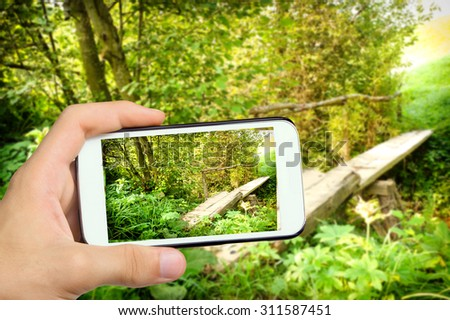 Hands taking photo landscape with a wooden bridge over a river  with smartphone. - stock photo