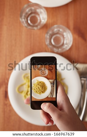 Hands taking photo of Italian pasta lunch with smartphone - stock photo