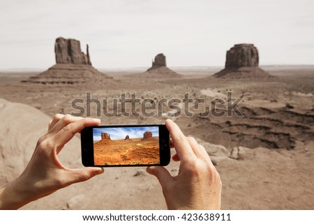 hands taking picture at the monument valley with a smart phone - stock photo