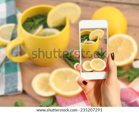 Hands taking picture of hot tea - stock photo