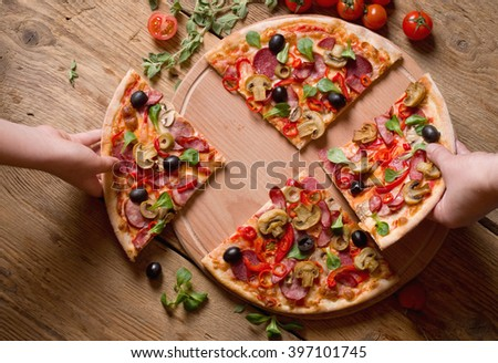 hands taking slices of pizza - stock photo
