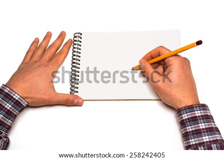 Hands that draw on a white notepad  - first person view - stock photo