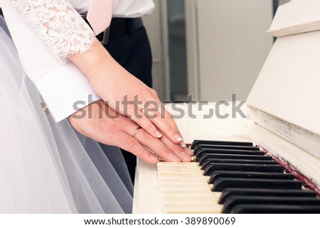 hands the newlywed on grand piano keys - stock photo
