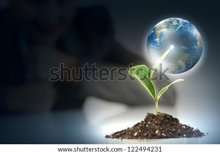 hands, the young sprout and our planet Earth. Elements of this image are furnished by NASA