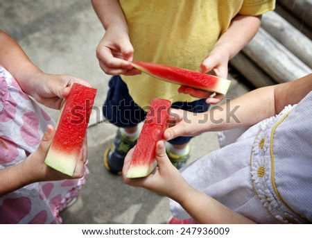 Hands three kids holding pieces of watermelon - stock photo