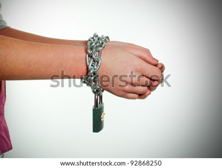 Hands tied up with chains against light background