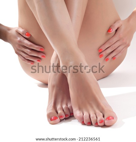 Hands touching beautiful woman's legs, isolated on white