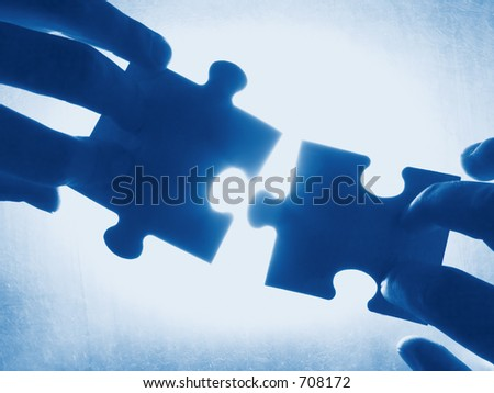 hands trying to fit two puzzle pieces together - stock photo