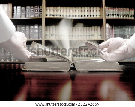 Hands turning pages in old law book with library in background - stock photo