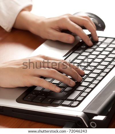 Hands typing on a notebook keyboard