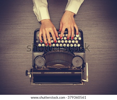 Hands typing on a Vintage typewriter. View from above - stock photo