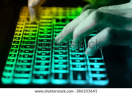 hands typing on keyboard in green light with motion blur,Concept for cybercrime hack cloud security - stock photo